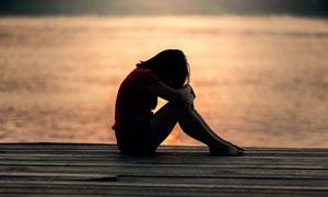 湖边坐着的逆光美女摄影图片