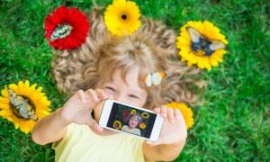 草地上拿手机自拍的小女孩高清图片