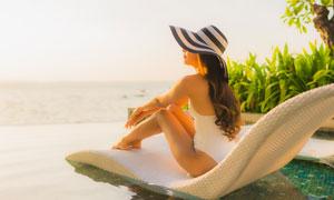 海边泳池躺椅上坐着的美女高清图片