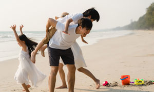 海邊玩沙子的親子人物攝影高清圖片