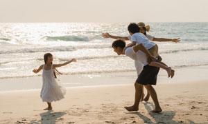 在沙灘上追逐嬉戲的一家人高清圖片