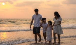 沙灘上手拉著手的大人小孩高清圖片