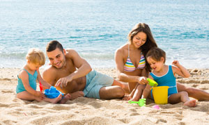在沙灘上陪著小孩玩的父母高清圖片