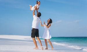 海灘上的幸福三口之家攝影高清圖片
