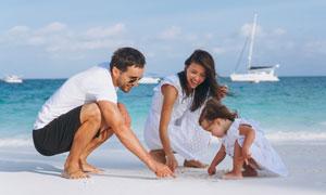 在沙灘上寫字的一家人攝影高清圖片