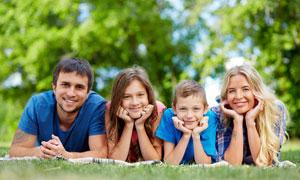 趴在青草地上的一家人攝影高清圖片