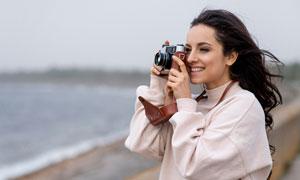 拿起照相机拍摄美景的美女高清图片