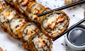 筷子夹起的脆皮寿司卷摄影高清图片