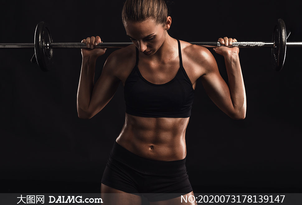 肩上扛杠铃的肌肉美女摄影高清图片