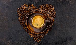 咖啡杯与摆成心形的咖啡豆高清图片