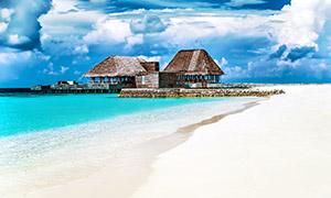 蓝天白云大海沙滩与茅草屋高清图片