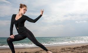 在海边做拉伸动作的运动美女摄影图片
