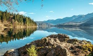 蓝天下的山林和湖泊倒影摄影图片