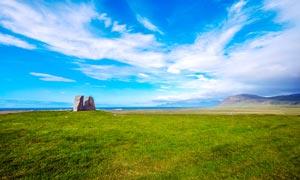 蓝天白云下的草地和石头摄影图片