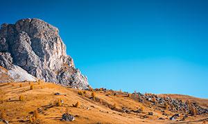 蓝天下的山坡和石头摄影图片