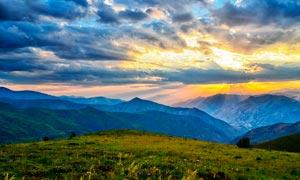 乌云下的山顶和夕阳美景摄影图片
