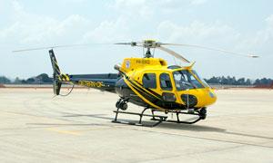 飛機場停泊的黃色直升機攝影圖片