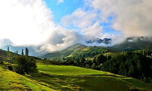 云霧繚繞的綠色山坡攝影圖片