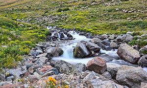 山腳下的小溪流水和石頭攝影圖片