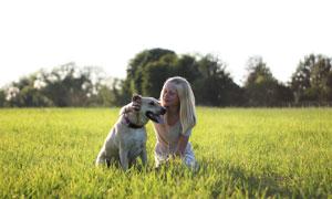 在草地上与狗狗互动的女孩高清图片
