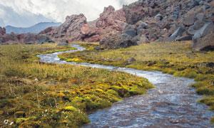流经山脚下草地的溪水摄影高清图片