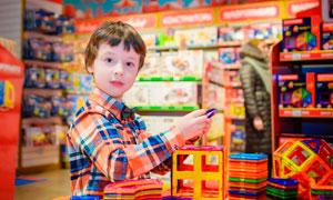 玩具店中玩磁力片的小男孩摄影图片