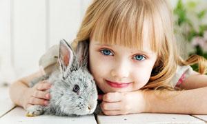 抱着小兔子趴在桌子上的小女孩摄影图片