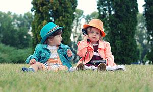 在草地上玩耍的男孩和女孩摄影图片