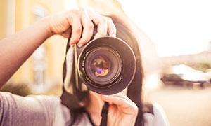 手拿著單反相機拍照的女孩攝影圖片