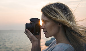 在海邊拍照的美女攝影師攝影圖片