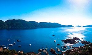 阳光下的蓝色湖泊全景摄影图片