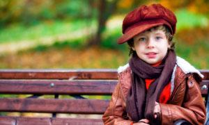 公园里坐在靠椅上的小男孩摄影图片
