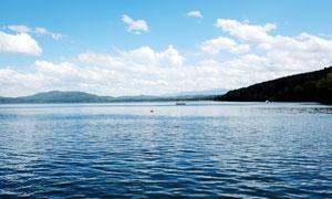 蓝天白云下的蓝色湖泊摄影图片