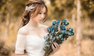 手里拿著藍色玫瑰花的美女攝影圖片