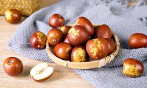 桌上竹盘子里的新鲜红枣摄影图片