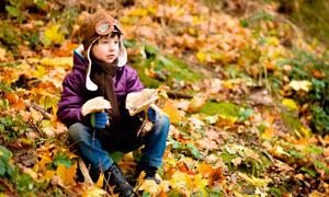 在山坡落叶中坐着的小男孩摄影图片