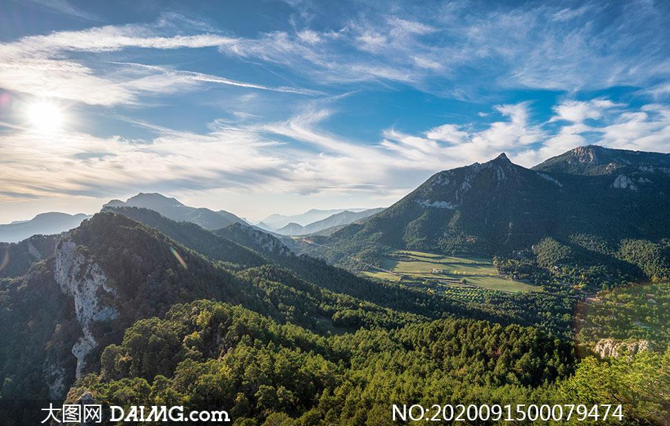 蓝天白云下的山峰和山林摄影图片