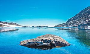 蓝天下的湖泊和湖中岩石摄影图片