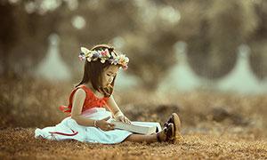 做在草地上看书的小女孩摄影图片