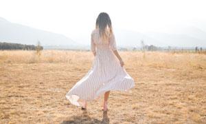 秋天草地上的美女背影摄影图片