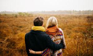 秋季田园中散步的情侣背影摄影图片