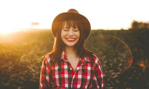 夕阳下戴着帽子的美女摄影图片