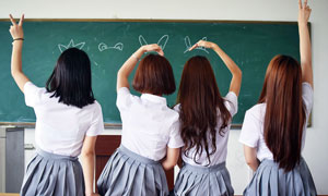 黑板前穿着校服的学生背影摄影图片