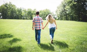 在草地上散步的情侣背影摄影图片