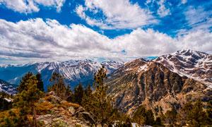 藍天白云下的雪山山頂景觀攝影圖片