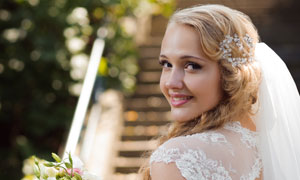 手着拿鲜花的金发新娘回眸摄影图片