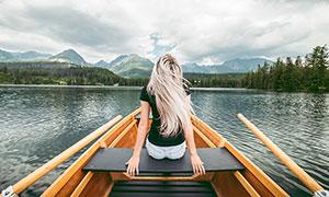 坐在湖中小舟上的美女摄影图片