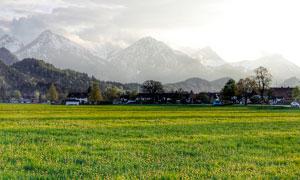 雪山脚下的草地和村庄高清摄影图片