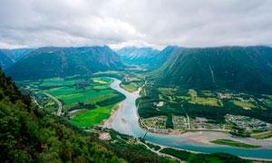 青山脚下的河流和村镇摄影图片