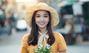 手拿着花朵带着帽子的女生摄影图片